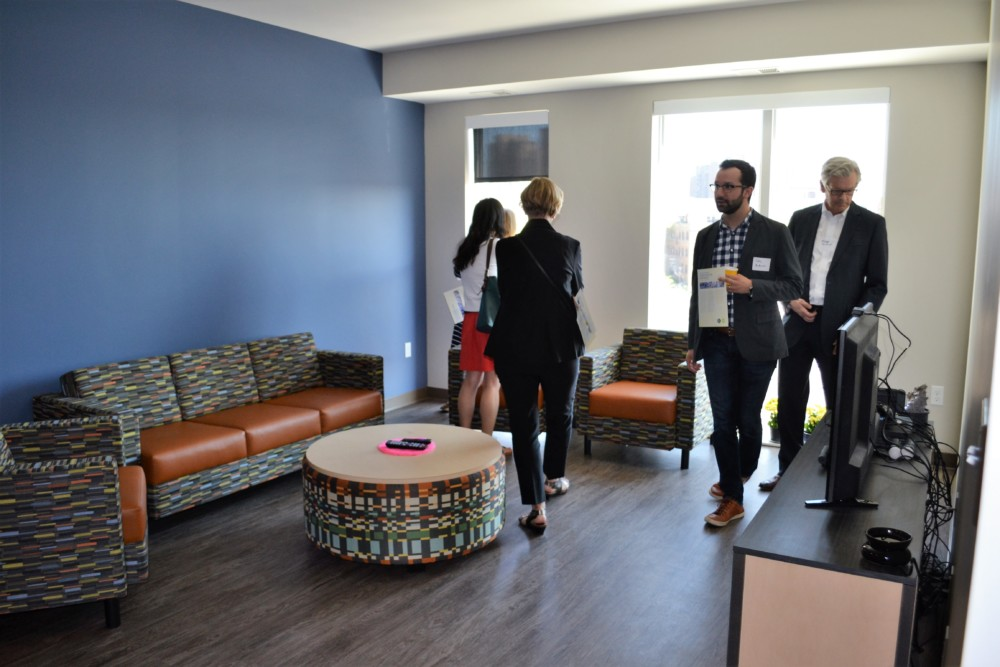 """Visitors explore the central space of a """"quad"""" of four apartments at the grand opening of Downtown View"""