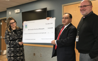 Three people holding a giant check